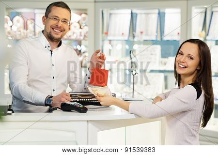 Woman paying with cash in jewellery shop