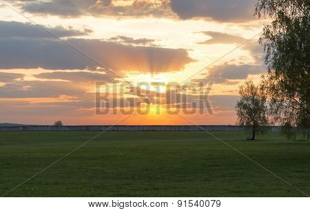 Sunset Over Expansive Green Field