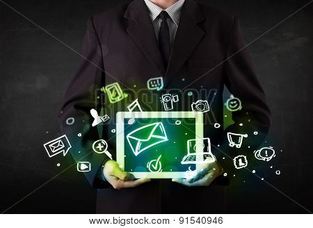 Person holding a white tablet with media icons and symbols