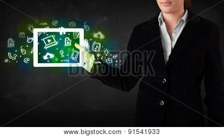 Person holding tablet pc with green media icons and symbols