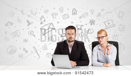 Business man and woman sitting at table with hand drawn media icons and symbols