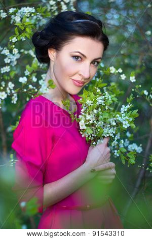 Beautiful Brunette Woman In Pink Dress In Blooming Cherry Tree Garden