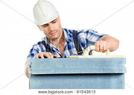 Male builder in working clothes, helmet and tools. Isolated over white.