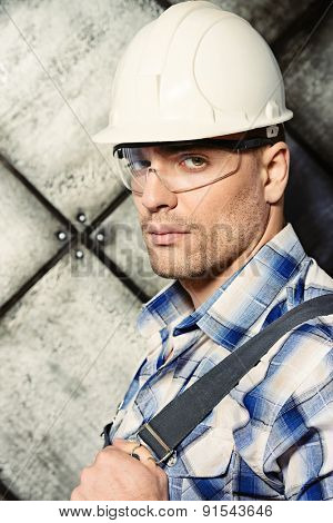 Close-up portrait of a handsome costruction worker standing in uniform and helmet over grunge industrial background. Job, occupation.