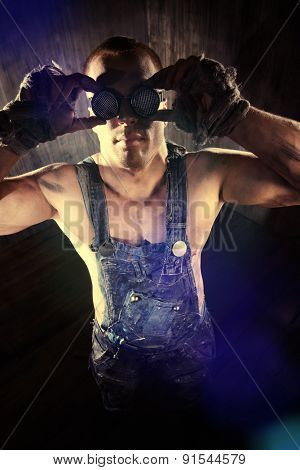 Brutal muscular dirty man in goggles over dark grunge background. Mining industry. World of the future, Apocalypse.