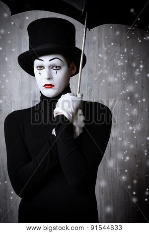 Portrait of a male mime artist standing under umbrella expressing sadness and loneliness. Grunge background.