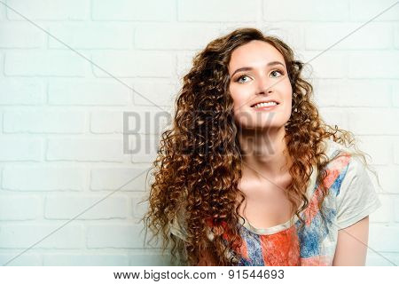 Pretty smiling teenage girl posing by the brick wall. Casual jeans style.