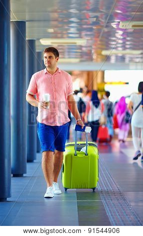 Young Adult Man Walking Through Crowded International Airport