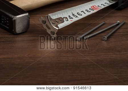 Hammer with steel tape and three nails on table