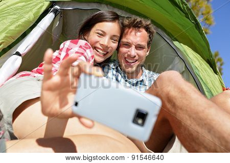 Camping couple in tent taking selfie using smartphone. Campers self portrait photo picture. Woman and man smiling happy outdoors in forest. Happy people having fun. Asian woman, Caucasian man.