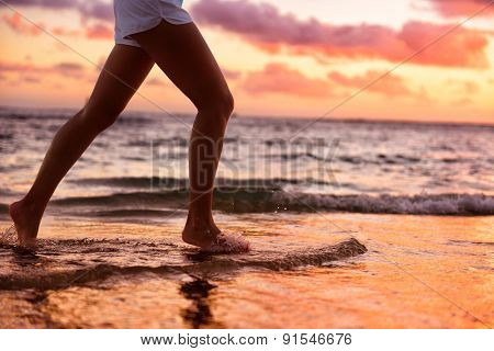 Running woman jogging barefoot in water at beach sunset. Close up of female feet of runner splashing in the edge of water. Girl training alone.