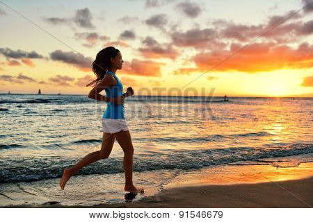 Woman running and jogging training at beach sunrise. Female runner working out exercising alone on run. Fit girl fitness model.