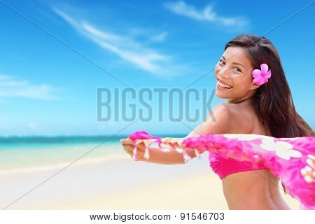 Beach woman in bikini happy on vacation paradise beach waving scarf sarong in wind happy in on travel holiday in tropical Hawaii an beach. Beautiful biracial Asian Caucasian girl.