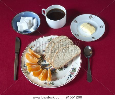 Breakfast set with coffee, bread, butter and orange wedges on a red tablecloth