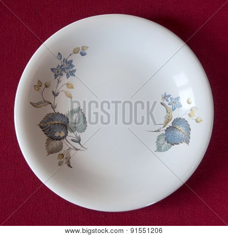 Empty decorated plate on a red tablecloth