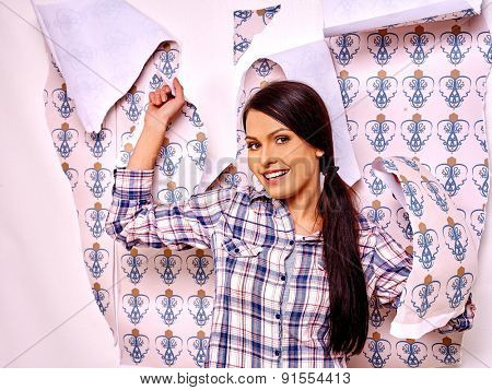 Happy young woman glues wallpaper at home.