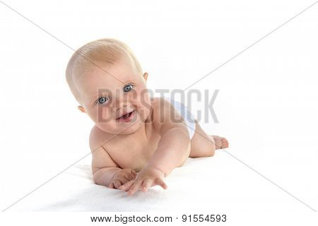 baby girl child lying down on white blanket smiling happy portrait face studio shot isolated on white caucasian