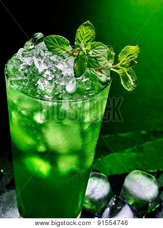 Green drink  with ice and mint leaf on dark background.