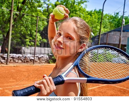 Teenager girl athlete holding  racket and ball on  brown tennis court.