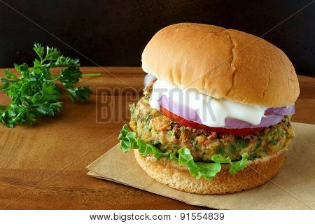 Falafel burger with lettuce, tomato, onion and tzatziki sauce