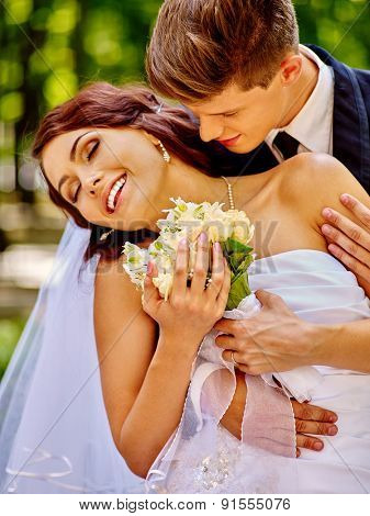 Bride and groom with flower kissing on summer  outdoor.
