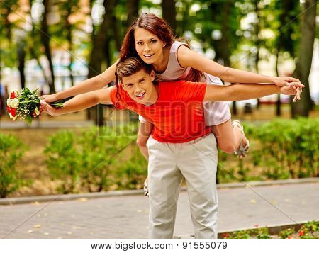 Couple with flower playing at park. Outdoor date.