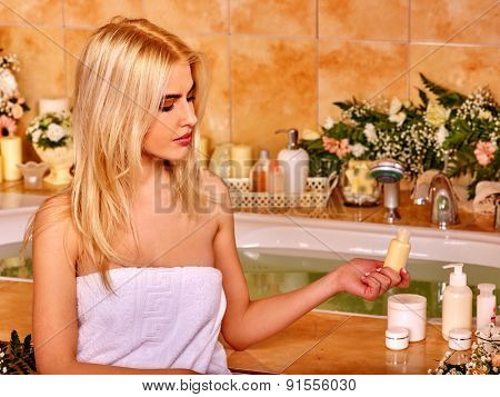 Blonde woman relaxing at flower water spa. Holding bottle.