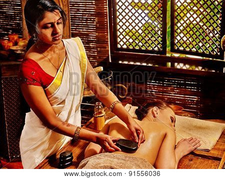 Young woman having Indian stone massage.