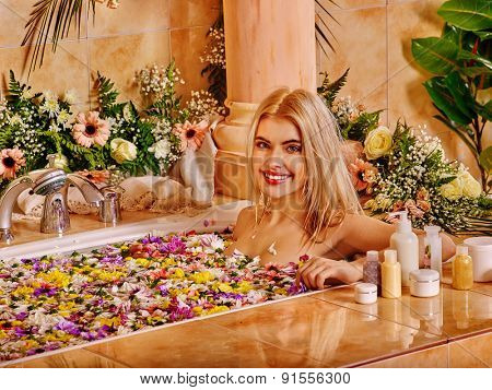 Woman relaxing at flowers water spa. Luxury bath.