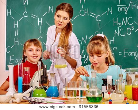 Teacher with children holding flask in chemistry class. Green blackboard.