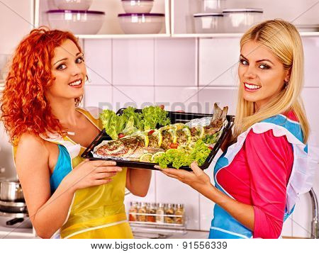 Happy women prepare grilled fish in oven.