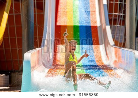Happy child girl in bikini showing thumb up sliding water park.