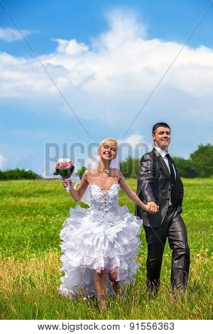 Couple wedding with flower  running on green grass outdoor.