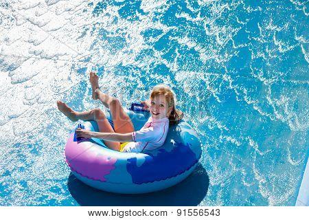 Children  at ring  on water slide at aquapark. Summer holiday.