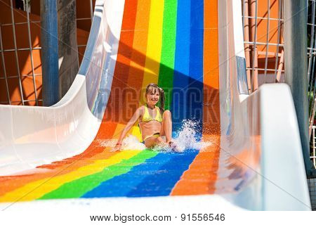 Children  on water striped slide at aquapark. Summer holiday.