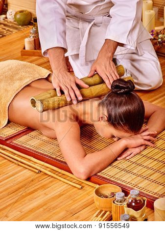 Young woman with forehead on hands getting bamboo massage. Male therapist.