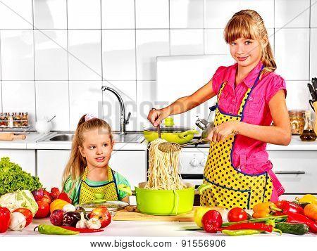 Children  cooking spaghetti at kitchen.