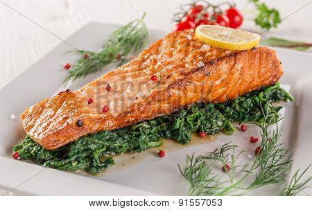 Salmon steak with spinach on white plate, close-up