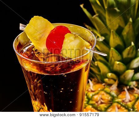 Champagne cocktail with cherry and whole pineapple with leaves . Top view