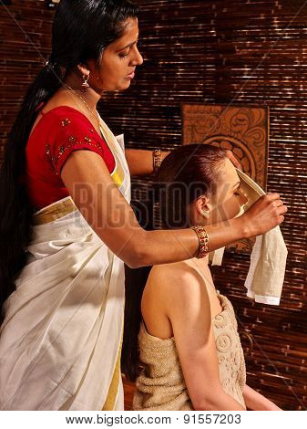 Young woman having head ayurveda spa treatment in India salon.