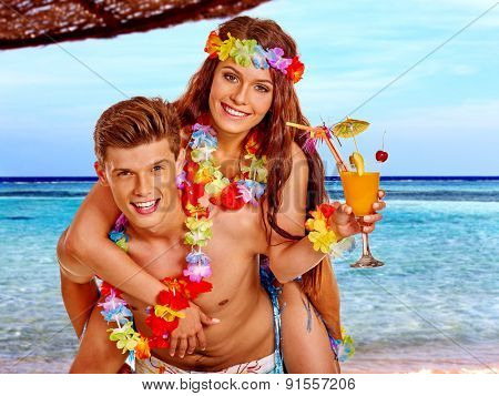 Couple with cocktail at Hawaii wreath beach near blue sea. Summer outdoor.