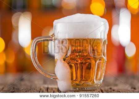 Glass of beer on bar desk, close-up.