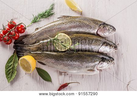 Rainbow trouts on white wooden table, close-up