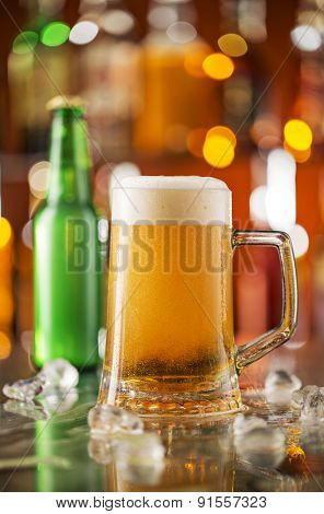 Bottle of beer with glass on bar desk, close-up.