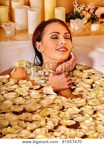 Woman relaxing in white rose petal at water spa.