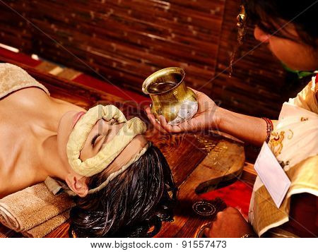Woman having facial dough oil eyes mask at ayurveda spa.
