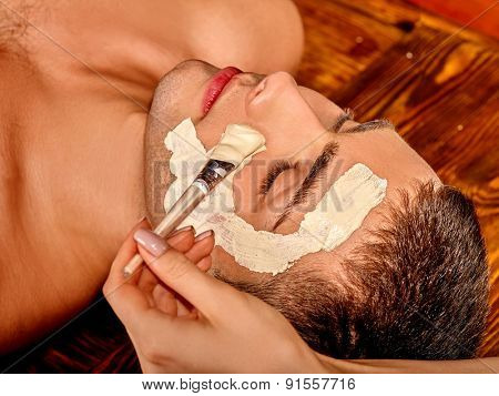 Man getting clay facial mask in beauty spa.