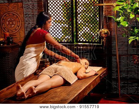 Young caucaswian woman having oil India spa treatment.