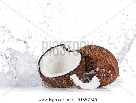 Cracked coconuts with water splash on white background, close-up.
