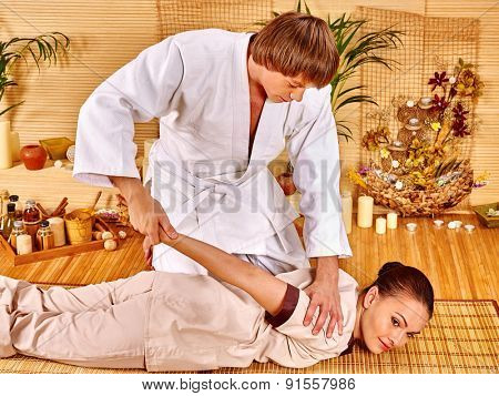 Handsome man makes massage girl in spa bamboo.